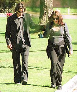 Keanu Reeves dressed in black arm in arm with his girlfriend